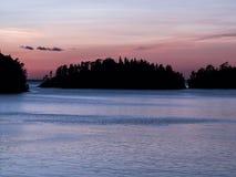 Zonsondergang Silhouetten van eilanden op de horizon Tint in koude kleuren Stock Foto's