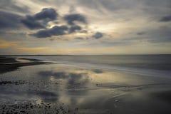 Zonsondergang tegen een bewolkte dag op het strand stock afbeelding