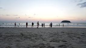Zonsondergang timelapse op het strand Weergeven van het eiland, de oceaan, de mensen, de golven, de rode zon en het zand stock video