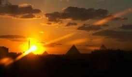 Zonsondergang van een piramide en een moskee Stock Afbeeldingen