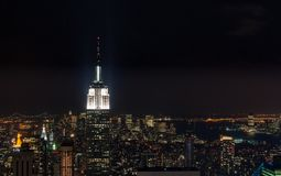 Zonsondergang vanaf de bovenkant van de rots - Empire State Buildingtop stak helder links van het kader aan - in kleur stock foto