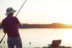In zonsondergang vissen en mensen die terwijl het genieten van van hobby ontspannen royalty-vrije stock afbeeldingen