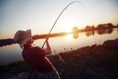In zonsondergang vissen en mensen die terwijl het genieten van van hobby ontspannen stock afbeeldingen