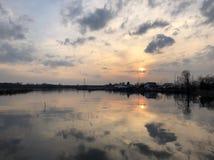 Zonsondergangbezinningen met wolken royalty-vrije stock afbeelding