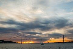 Zonsonderganghemel boven Tagus-Rivier, Brug 25 April Lissabon en haven bij van schip, Portugal Royalty-vrije Stock Afbeelding