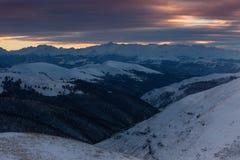 Zonsonderganghemel in de wolken over de bergen met sneeuw worden behandeld die Stock Foto's