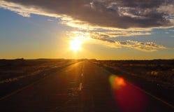 Zonsonderganghemel en weg in de woestijn stock foto