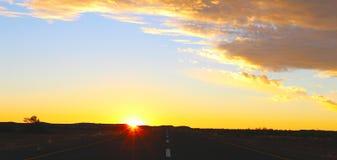 Zonsonderganghemel en weg in de woestijn stock afbeeldingen