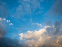 Zonsonderganghemel met donkere en witte wolken die zon op stralen wijzen Stock Foto's