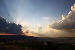 Zonsonderganghemel met wolken over Arabische stad stock afbeeldingen