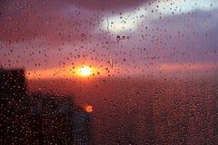 Zonsonderganghemel met wolken van de overzeese die en huisachtergrond door regendruppels op glas wordt gezien Royalty-vrije Stock Afbeeldingen