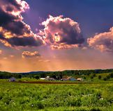 Zonsonderganghemel over een landbouwbedrijfhoeve stock afbeelding