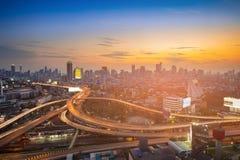 Zonsonderganghemel over stadszaken de stad in en wegkruising Royalty-vrije Stock Afbeelding
