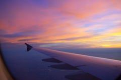 Zonsonderganghemel van het vliegtuigvenster Stock Afbeeldingen