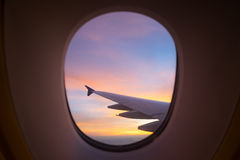 Zonsonderganghemel van het vliegtuigvenster Stock Foto's