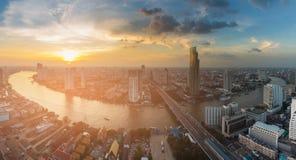 Zonsonderganghorizon over rivier gebogen de stadszaken van Bangkok de stad in Stock Foto's