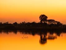 Zonsondergangkleur tijdens de avond van de waterkant stock foto