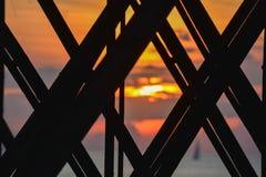 Zonsondergangkleuren zoals die door balken van de visserij van pijler worden gezien Stock Foto