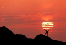 Zonsonderganglandschap met silhouet van een mens met op:heffen-omhooggaande wapens Stock Foto