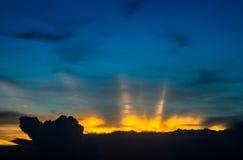 Zonsonderganglicht over de donkere wolken Stock Foto's