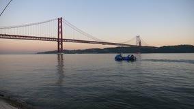 Zonsondergangmening de brug Lissabon met boot Portugal stock footage