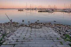 Zonsondergangmening die van baksteenweg in haven met jachthaven op achtergrond in Burlington, Ontario leiden royalty-vrije stock fotografie