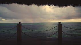 Zonsondergangmening van Caraïbische overzees en regenboog van houten pijler, de toevlucht van Punta Cana stock videobeelden