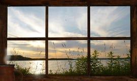 Zonsondergangmening van het meer uit het plattelandshuisjevenster. Stock Foto's
