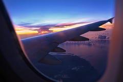 Zonsondergangmening van vliegtuigvenster Stock Foto