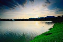 Zonsondergangogenblik dichtbij oever van het meer stock foto's