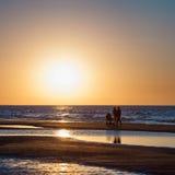 Zonsondergangoverzees en silhouetten van paar met kinderwagen Royalty-vrije Stock Foto
