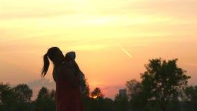 Zonsondergangsilhouet: jonge moeder die haar kind van de babyjongen in stadspark houden die zich voor het plaatsen van zon bevind stock video