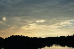 Zonsondergangsilhouet van boom bij meerkust tegen bewolkte blauwe hemel Stock Foto's