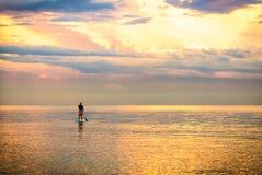 Zonsondergangsilhouet van een mens op tribune op peddelraad Royalty-vrije Stock Foto's