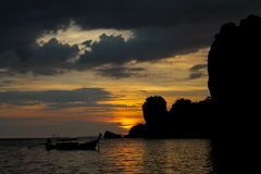 Zonsondergangsilhouet van rotsen en boot in baai in Thailand Royalty-vrije Stock Afbeeldingen