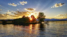 Zonsondergangstralen door bomen op het meer stock fotografie