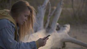 Zonsondergangstrand en meisje die smartphone voor het babbelen gebruiken stock video