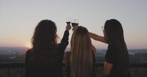 Zonsondergangtijd drie dames bij het balkon op de bovenkant van de bouw bewondert samen de zonsondergang allen en drinkend een gl stock video