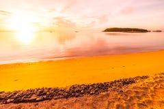 In zonsondergangtijd op het tropische strand en het overzees met kokospalm t Royalty-vrije Stock Afbeelding