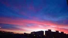 Zonsondergangwolken in stad stock foto's
