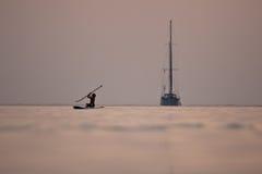 Zonsondergangzeilboot en jonge surfer Stock Fotografie