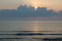 Zonsopgang achter wolk en kalme overzees Stock Fotografie