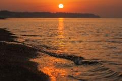 Zonsopgang bij het overzees Golven en kust in de stralen van de het toenemen zon Stock Afbeeldingen