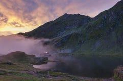 Zonsopgang bij ijzig Balea-Meer in een mistige ochtend, de Karpaten, Roemenië royalty-vrije stock foto's