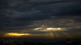 Zonsopgang door donkere wolken in de stad, stralen van lichte zichtbaar royalty-vrije stock fotografie