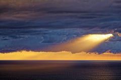 Zonsopgang door donkere wolken over oceaan met zonnestraal Stock Fotografie