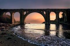 Zonsopgang in een brug over strand stock afbeeldingen