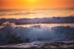 Zonsopgang en glanzende golven in oceaan Stock Foto