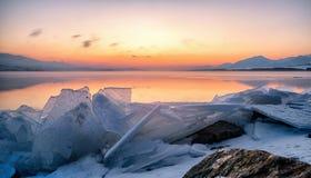 Zonsopgang en ijsschol bij meer stock afbeeldingen