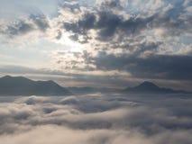 Zonsopgang en zonnestraal over berg met overzees van mist in voorgrond stock fotografie